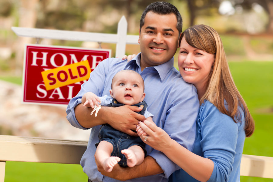 Couple with child in front of sold home